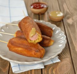 Plate of corn dogs with mustard and ketchup