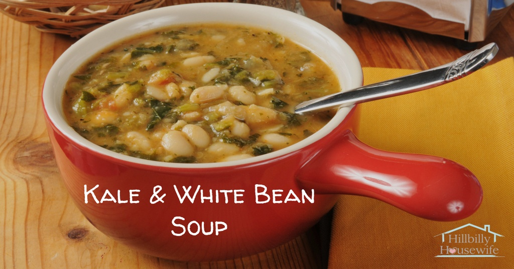 Kale and white bean soup in a red bowl on a wooden table.