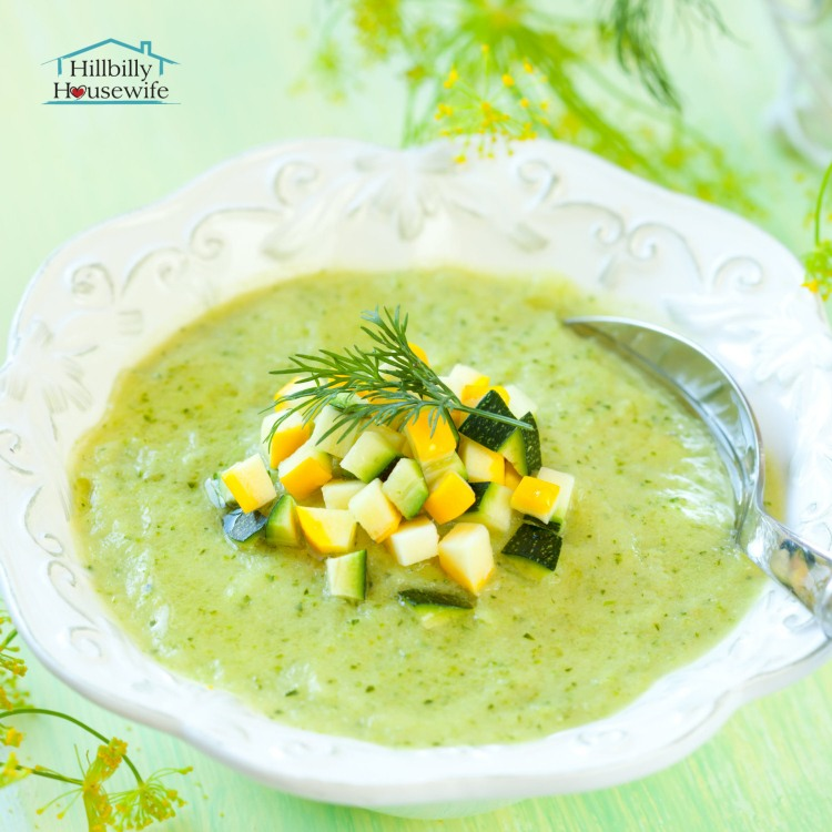 Bowl of Potato Zucchini soup on a green background with a spoon and chopped zucchini used as garnish.