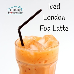 Tall glass of Iced London Fog Latte with a dark straw.. The Hillbilly Housewife Logo is in the background.