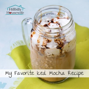 A mason jar of homemade iced mocha with whipped cream and chocolate syrup.