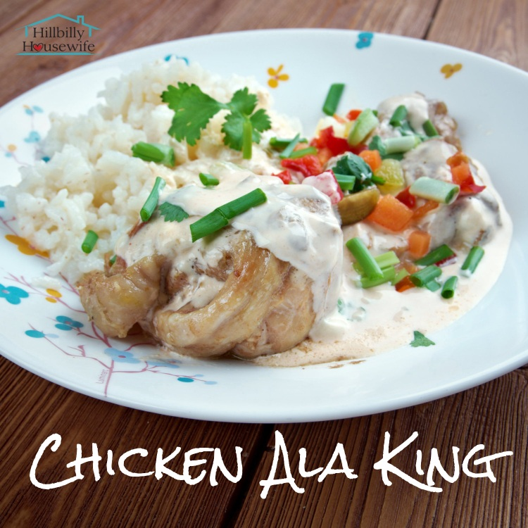 A plate of chicken ala king over a puff pastry with a side of vegetables and rice