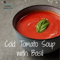 A bowl of cold tomato soup with a basil leave on top