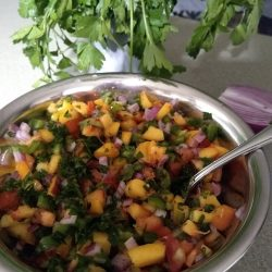 A bowl of fresh peach salad with a spoon. Herbs in the background