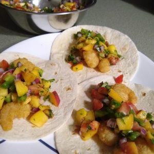 Fried shrimp tacos on flour tortillas with peach salsa